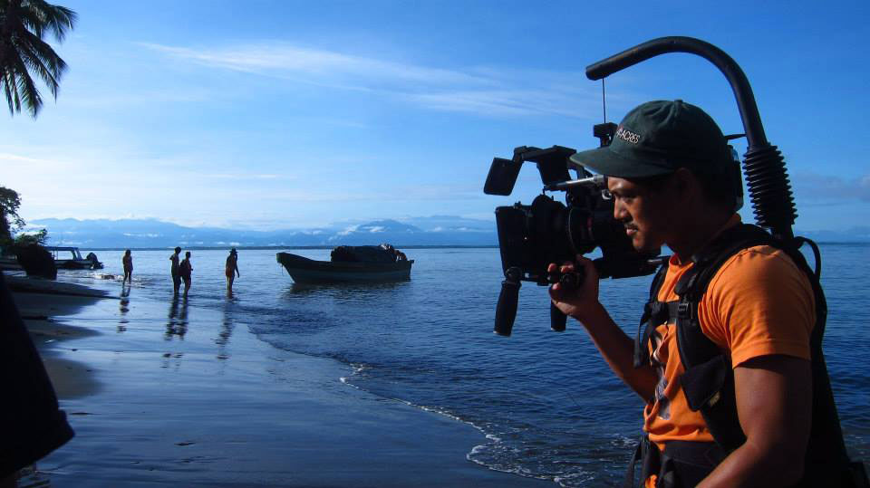 Photo of Alan Blanco operating a video camera on beach