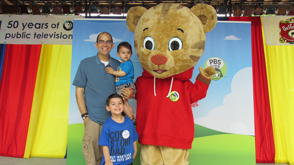 Daniel Tiger character posing with a family