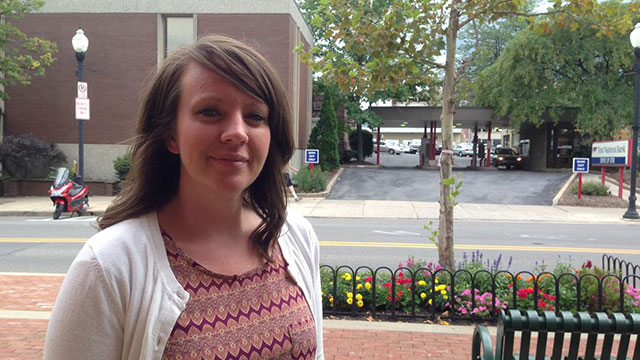 State College borough planner Meagan Tuttle stands in front of the old Verizon building and a bank that are part of the area targeted for redevelopment.