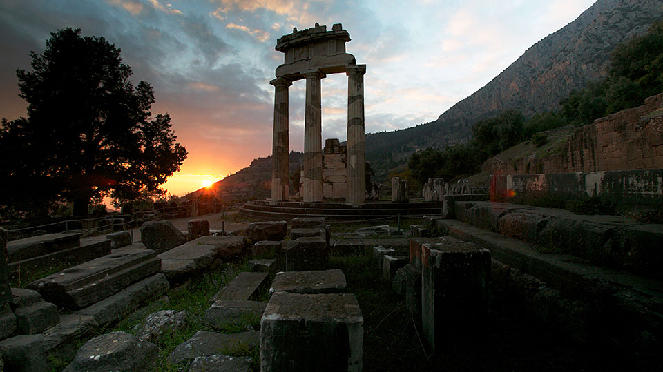 Sun sets behind the Temple of Athena at Delphi.