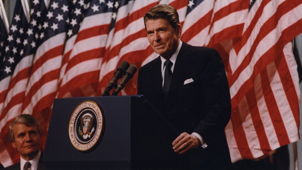 Ronald Reagan behind podium in front of American Flags