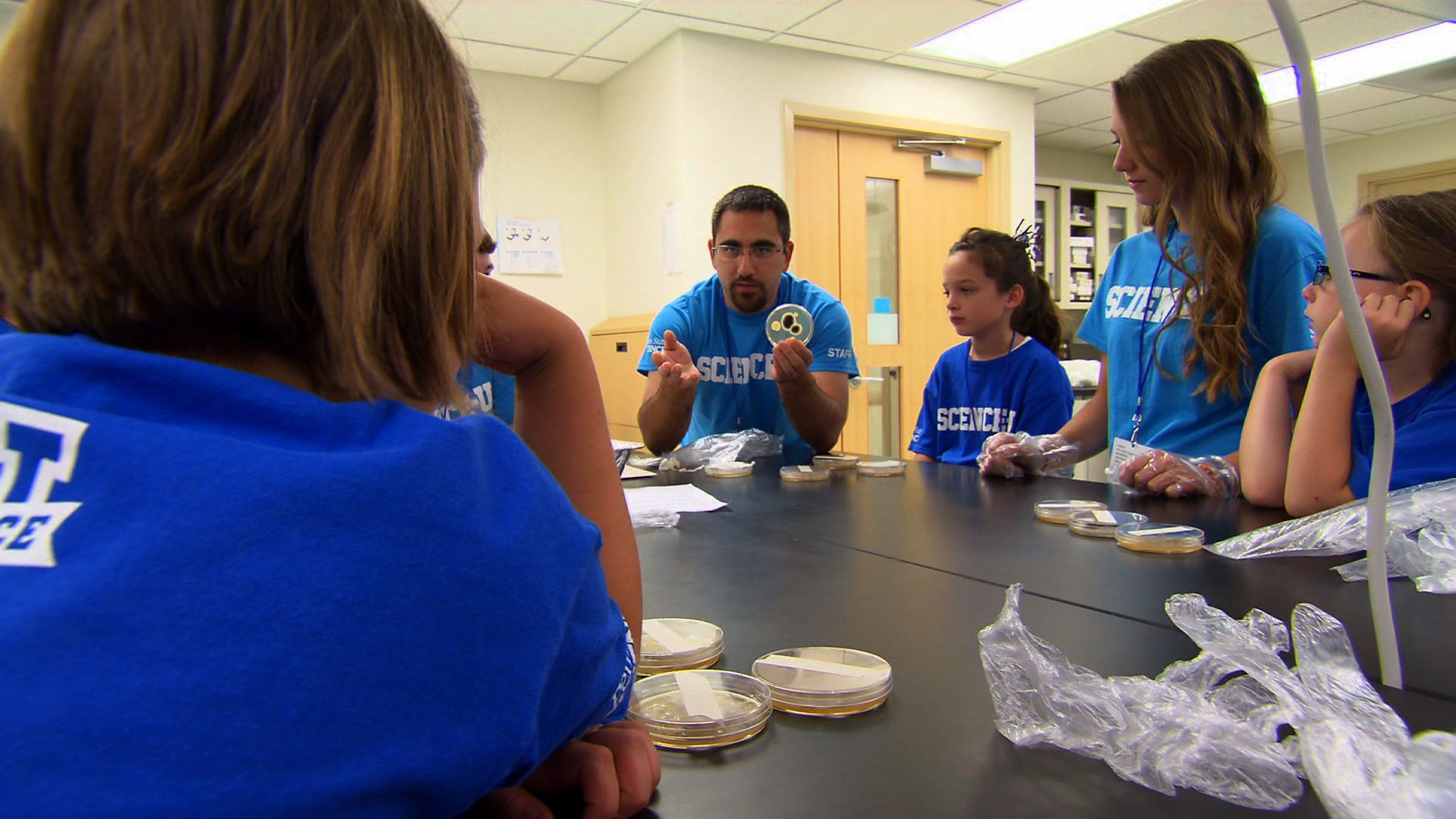 Instructor shows students petri dish