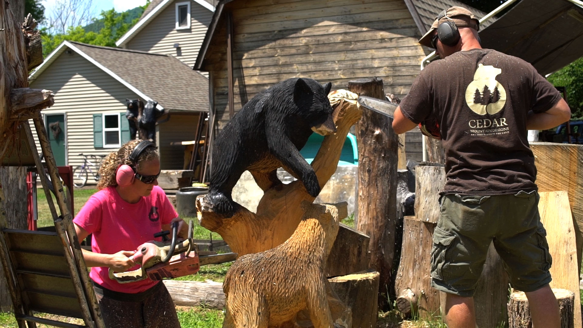 Cedar Mountains Design artists Heath and Hillary Bender carve a bear out of a log with chainsaws
