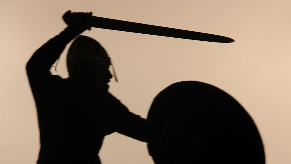 Silhouette of a Viking warrior with sword and shield.