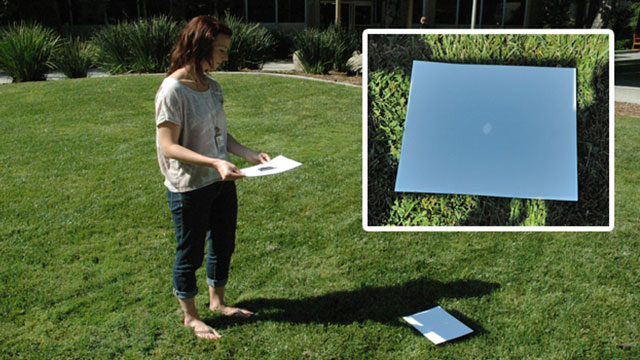 person demonstrating pinhole camera to watch eclipse
