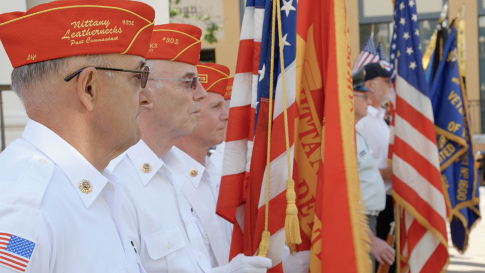 American veterans holding flags at memorial day ceremony