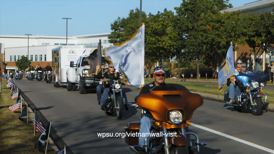 Motorcycles leading truck carrying travelling wall down Innovation Blvd