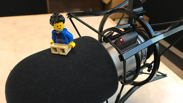 lego minifigure sitting on radio microphone