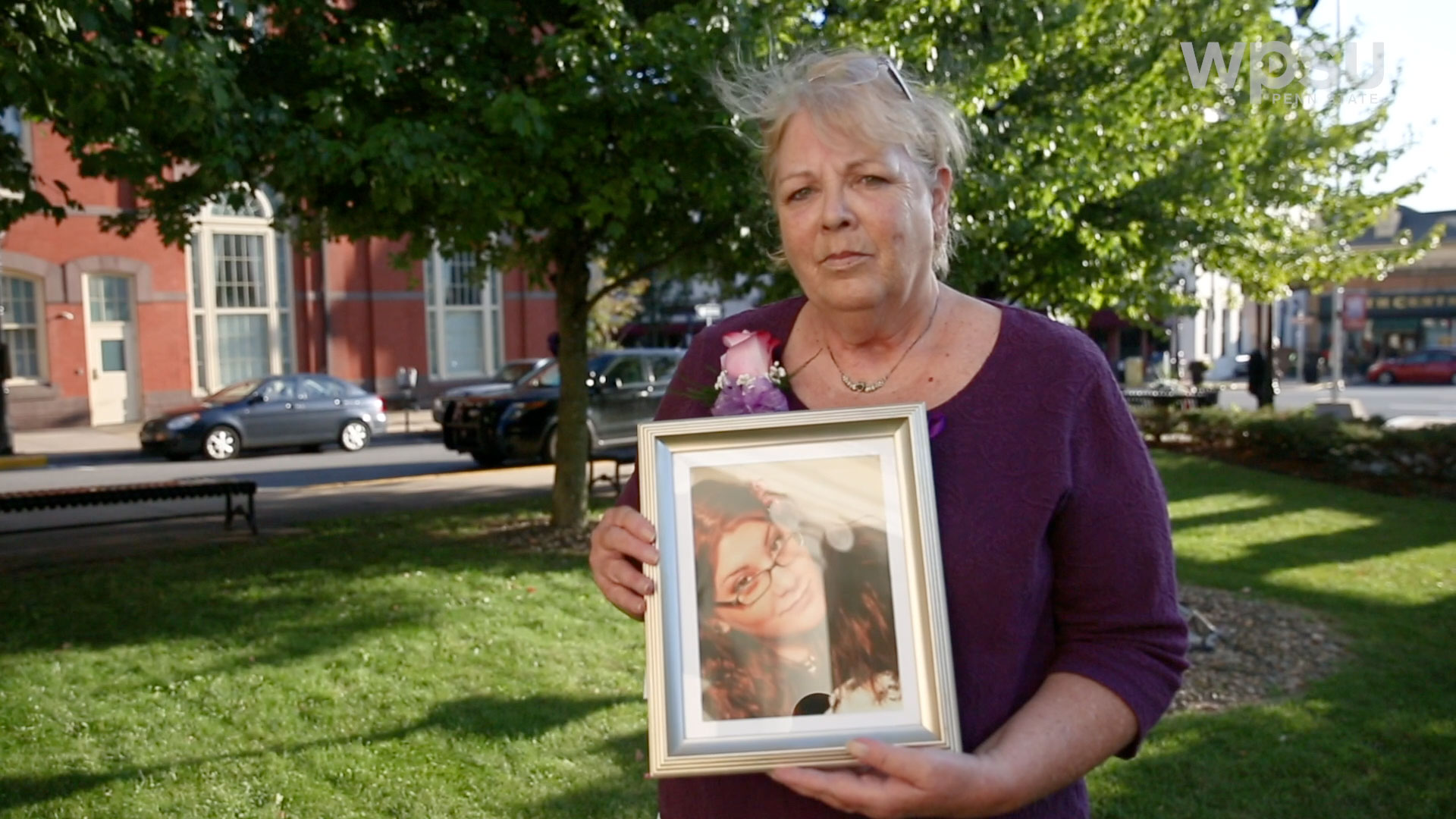 Older woman holding framed photo of young woman