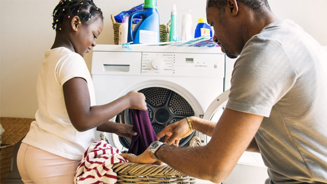 child helping adult with laundry