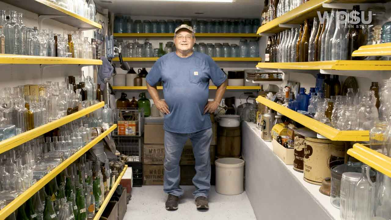 Person standing surrounded by shelves filled with antique bottles