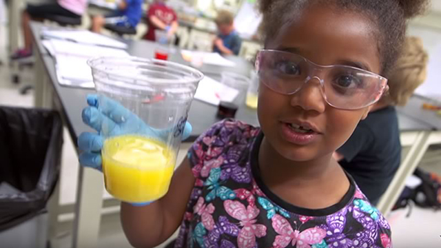 young girl holding a cup of orange juice