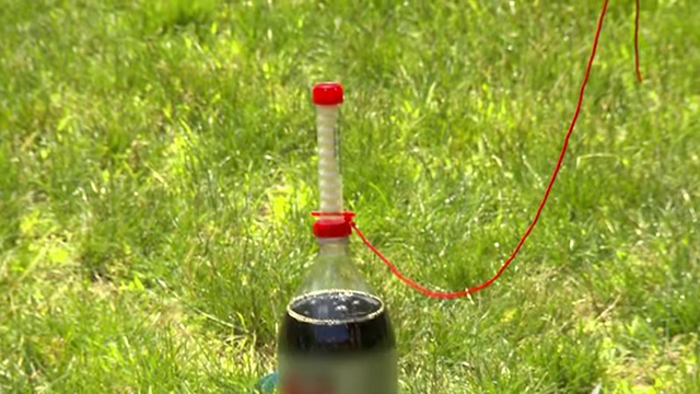 soda bottle with mentos stacked on top