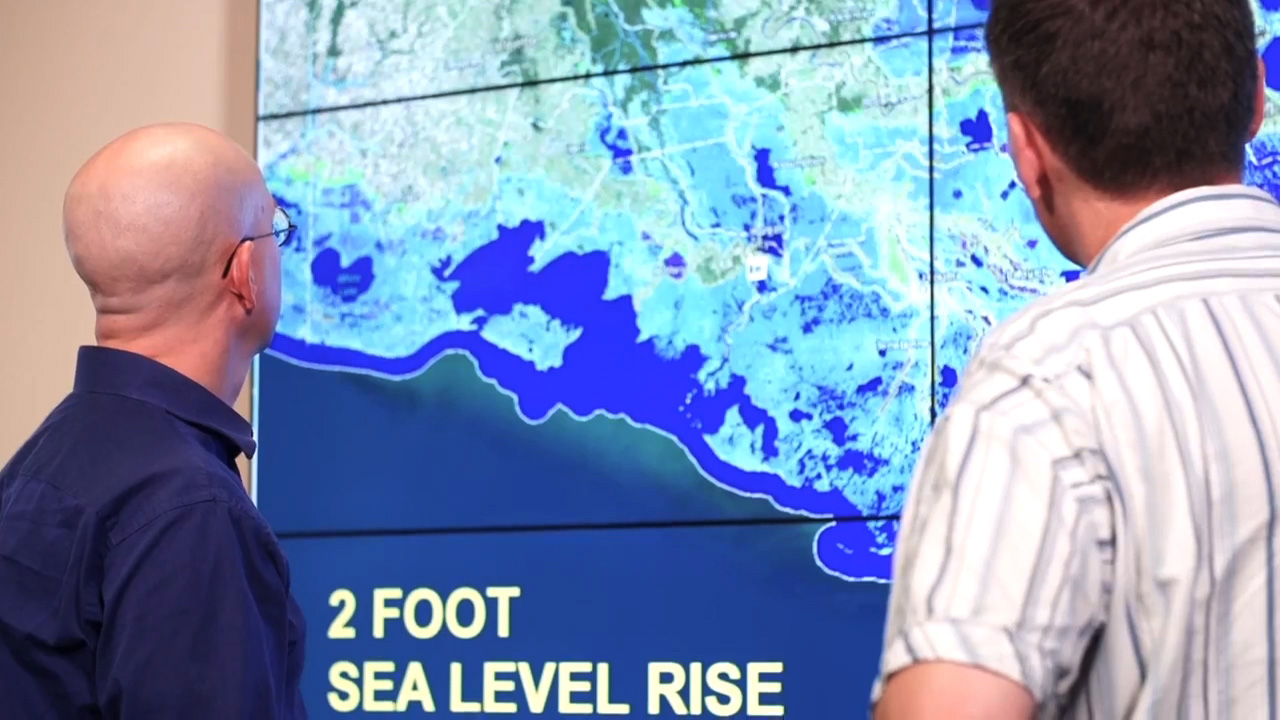 scientists looking at digital model of sea level projections