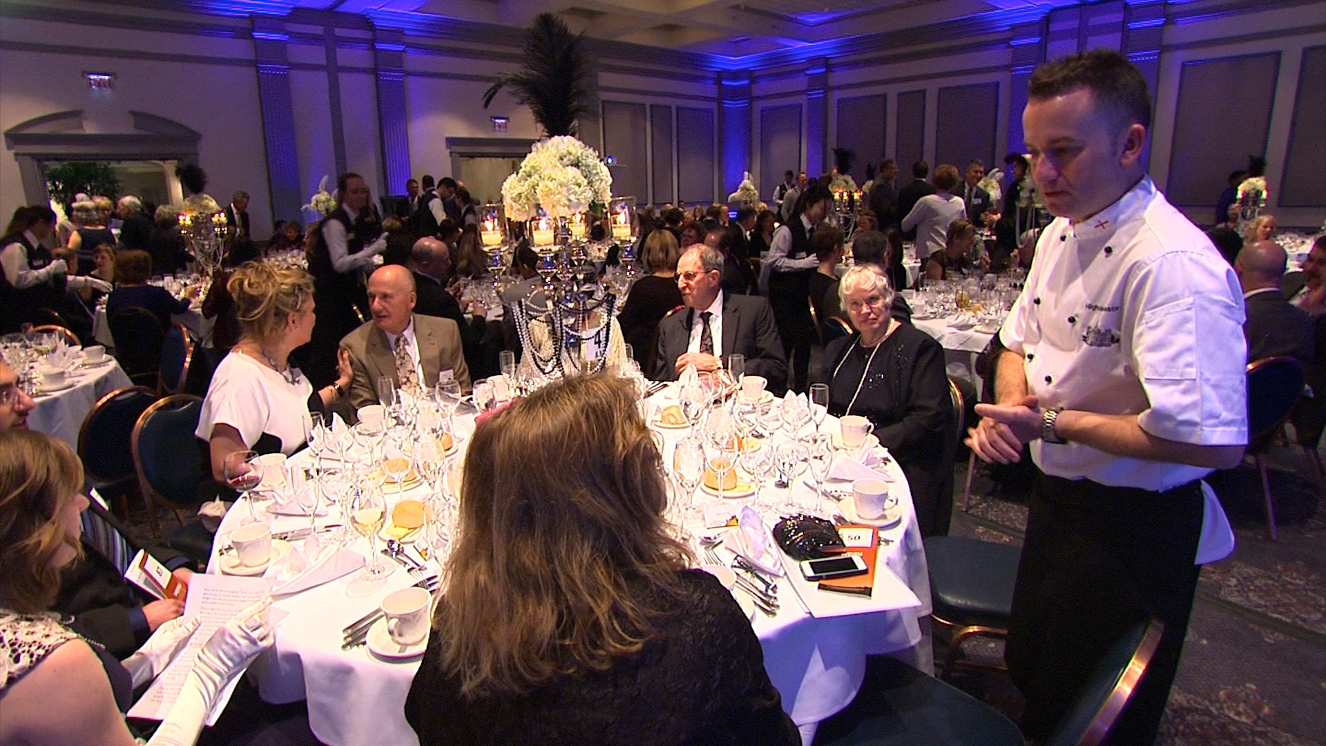 Chef Paul Brooke-Taylor having a discussion with seated dinner guests at the 2015 WPSU Connoisseur's Dinner