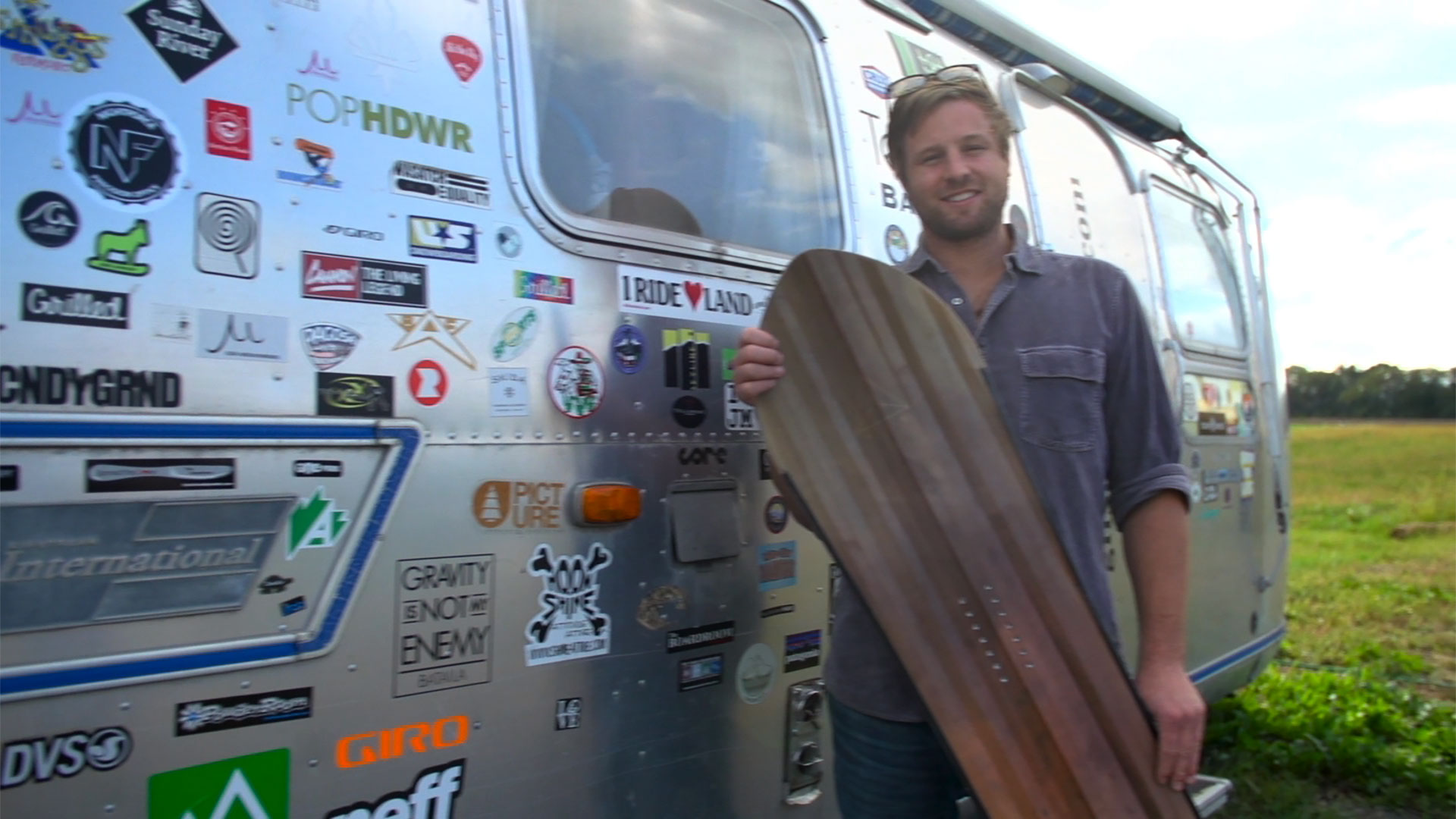 Man holding a snowboard standing in front of an airstream trailer covered in decals