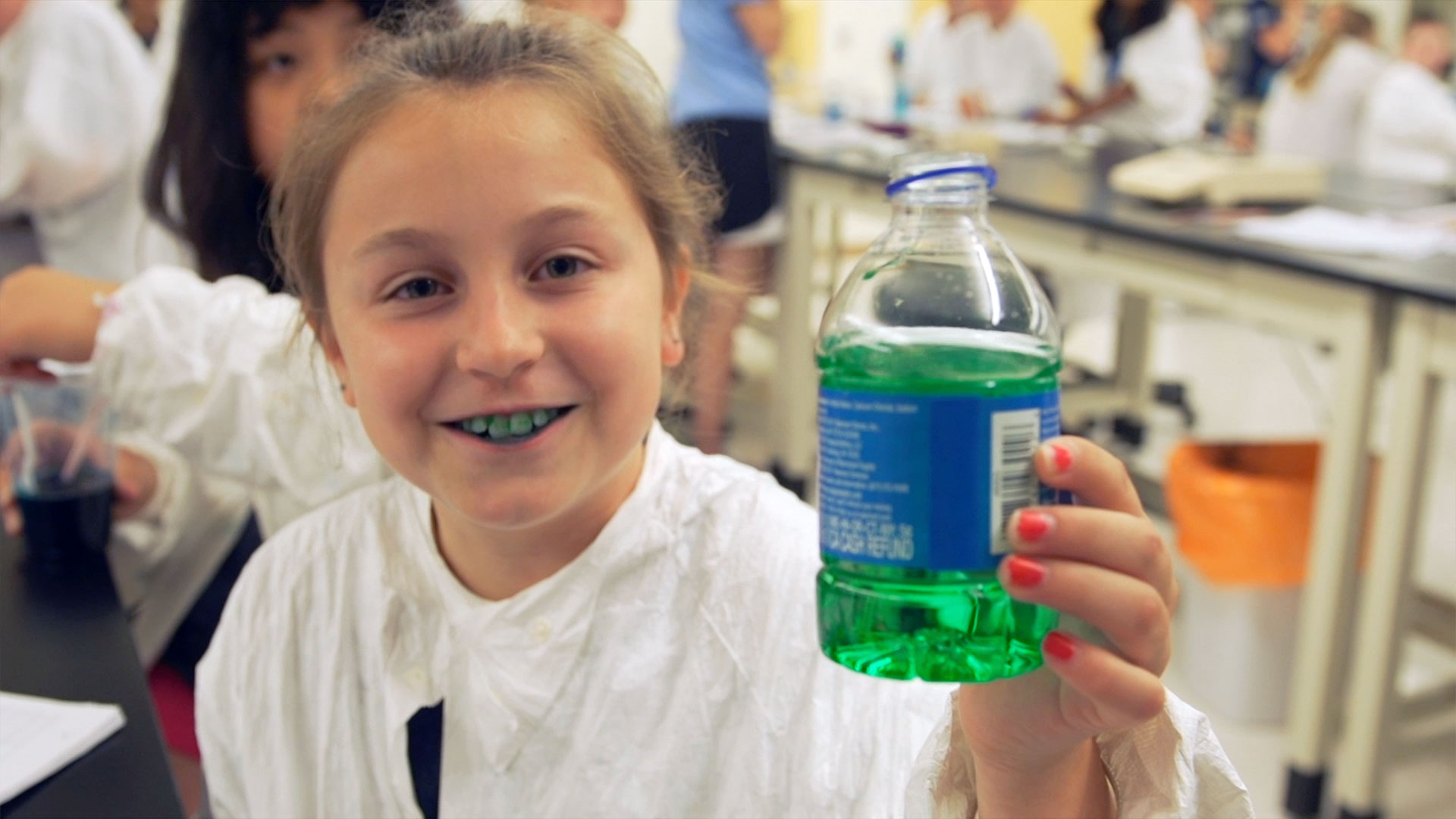 Young girl shows water bottle dyed green from the food coloring in her mouth