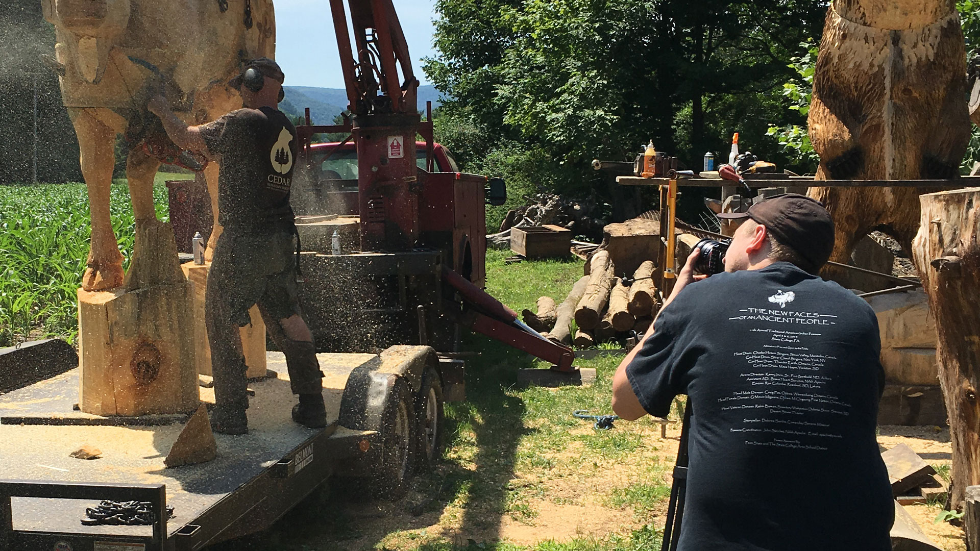 Videographer filming a chainsaw artist carving a cow