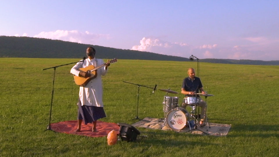 Guitar player and drummer performing in an open grass field