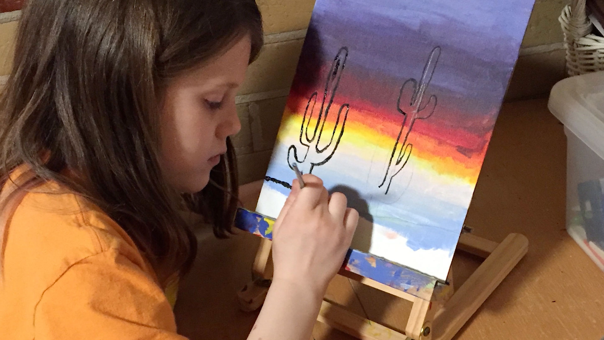 Claire North-Smyers painting on a canvas