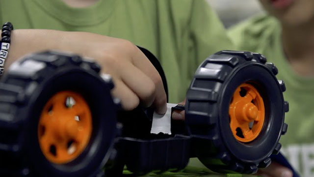 person repairing axel of toy truck