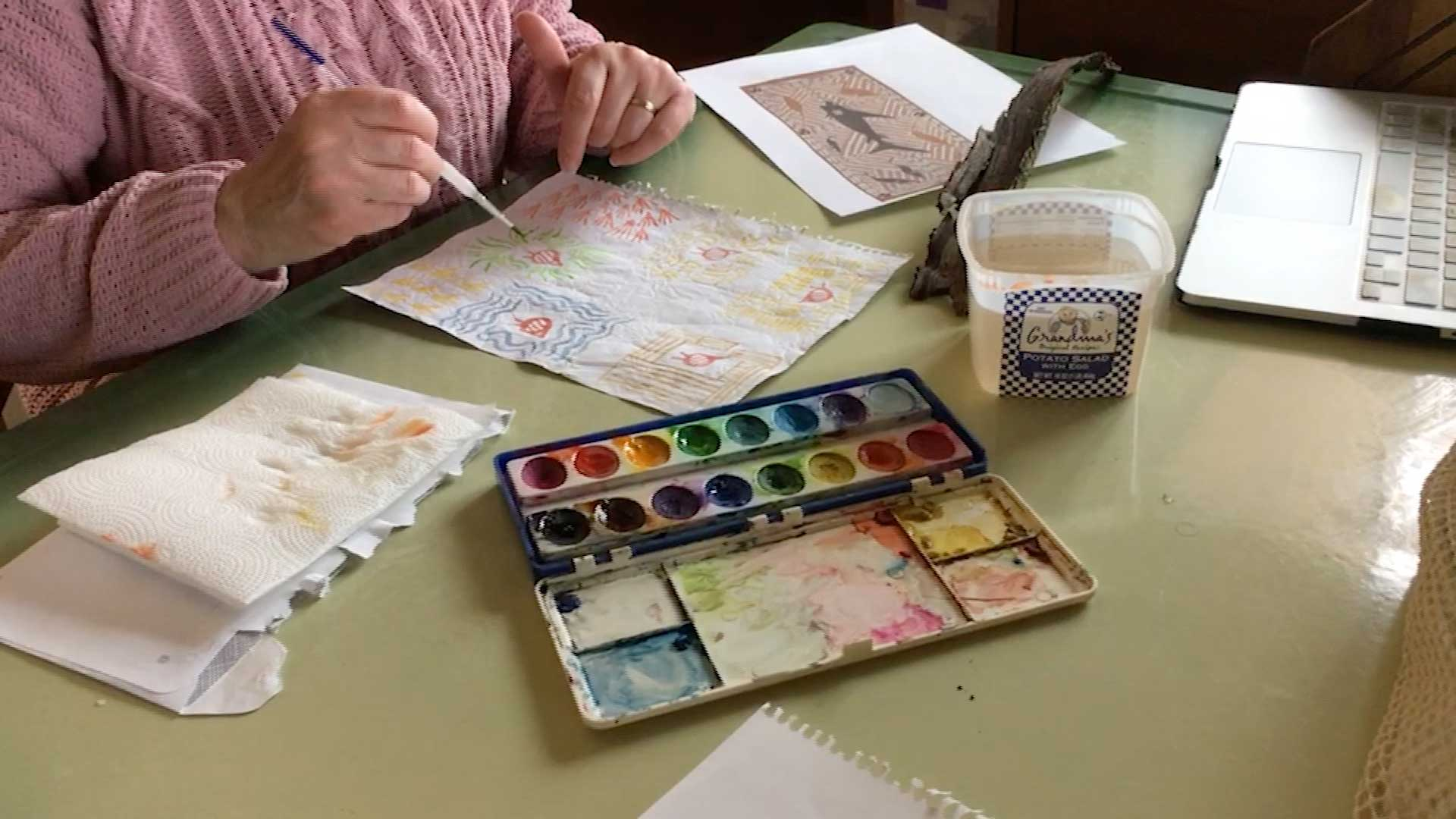 person painting with water colors